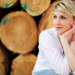 Thoughtful Woman Against Logs — Stock Photo #27253689