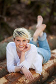 Happy Blond Woman Lying On Logs — Stock Photo
