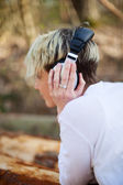 Rear View Of Woman With Headphones Lying On Log — Stock Photo