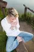 Woman Sneezing Into Handkerchief By Lake — Stock Photo
