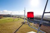 Obstruction léger avec des éoliennes en arrière-plan — Photo