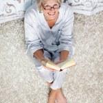 Старший женщина, держащая книгу сидя на ковер в спальне — Стоковое фото
