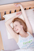 Woman With Arms Raised Lying In Bed — Stock Photo