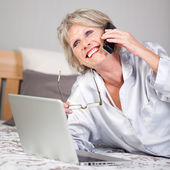 Woman With Laptop Using Cordless Phone In Bed — Stock Photo