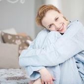 Kvinna kramas knä sittande i sängen — Stockfoto