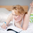 Writing woman lying in bed — Stock Photo