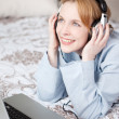Happy young woman listening to music in bedroom — Stock Photo
