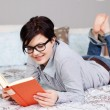 Woman Wearing Glasses While Reading Book In Bed — Stock Photo