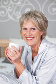 Senior Woman Holding Coffee Cup In Bedroom — Stock Photo