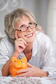 ベッドに横たわっている間見上げる piggybank を持つ女性 — ストック写真