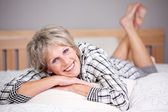 Happy senior female lying in bed — Stock Photo