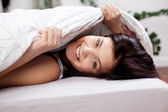 Woman Covering Herself In Comforter On Bed — Stock Photo