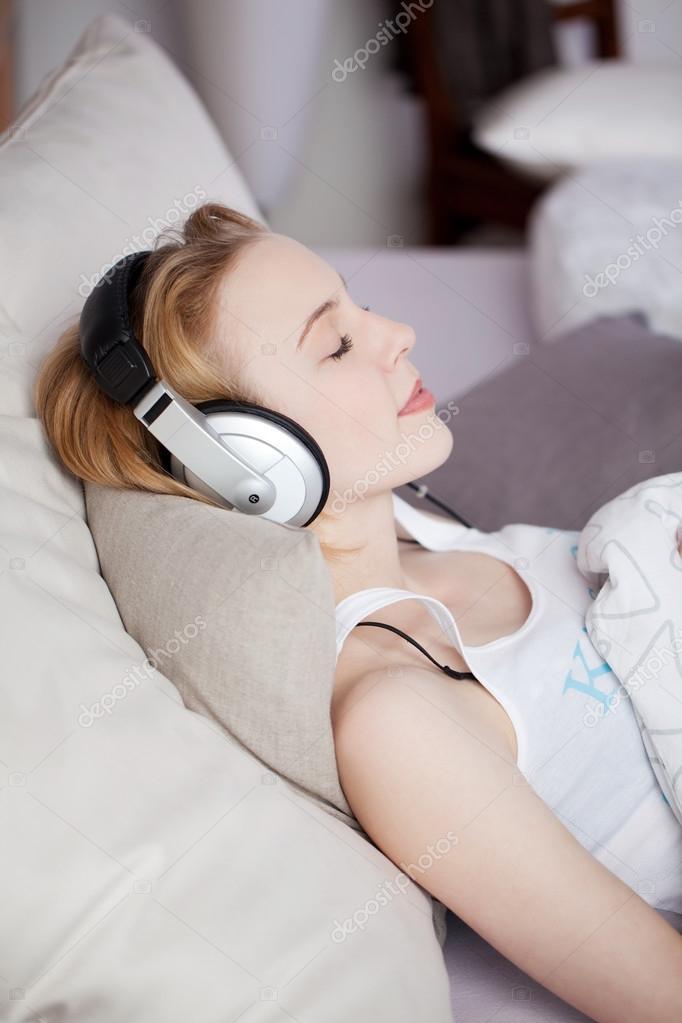 Femme coutant de la musique via le casque en position - Causes des vertiges en position couchee ...