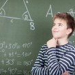 Young schoolboy standing near blackboard — Stock Photo #27312881