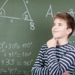 Young schoolboy standing near blackboard — Stock Photo