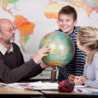 Teacher explain about globe to his students — Stock Photo #27313087