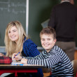 Classmates Sitting At Desk With Teacher Writing On Blackboard — Stock Photo