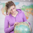 Schoolgirl pointing a place on a globe — Stock Photo #27313911