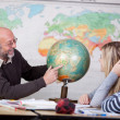 Teacher Pointing At Globe While Students Looking At It — Stock Photo