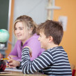 Cute kids learning geography in classroom — Stock Photo