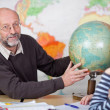 Stock Photo: Teacher teaching class about geography
