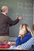 Teacher Solving Sums On Blackboard With Students In Foreground — Stock Photo