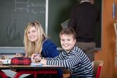 Classmates Sitting At Desk With Teacher Writing On Blackboard — Stock Photo