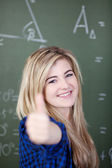 Girl Showing Thumbsup Sign Against Chalkboard — Stock Photo