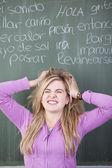 Gefrustreerd meisje met handen in het haar tegen schoolbord — Stockfoto