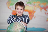 Preadolescent Child Leaning On Globe In Classroom — Стоковое фото