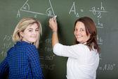 Teacher Writing On Chalkboard While Standing With Student — Stock Photo
