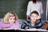Bored Students Leaning On Desk With Teacher In Background — Stock Photo