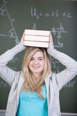 Female Student Carrying Stacked Books On Head Against Chalkboard — Stock Photo