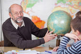 Teacher teaching the class about geography — Stock Photo