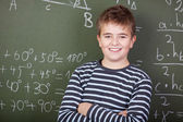 Smiling schoolboy standing near blackboard — Stock Photo