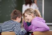 Macho y hembra estudiante chismes en aula — Foto de Stock