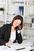 Zakenvrouw die aantekeningen maakt terwijl op de telefoon — Stockfoto