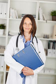 Female doctor carrying a large file — Stock Photo