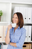 Woman enjoying a cup of coffee at the office — Stock Photo