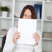 Businesswoman Holding Blank Paper In Front Of Face At Office — Stock Photo