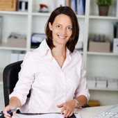 Confident Businesswoman Sitting At Office Desk — Stock Photo
