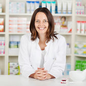 Pharmacist With Hands Clasped Leaning On Pharmacy Counter — Stock Photo