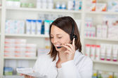 Smiling Pharmacist Conversing On Headset In Pharmacy — Stock Photo