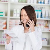 Pharmacist Holding Prescription Paper While Using Cordless Phone — Stock Photo
