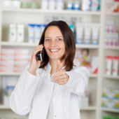Pharmacist Using Landline Phone While Gesturing Thumbsup — Stock Photo