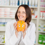 Pharmacist Holding Piggybank In Pharmacy — Stock Photo