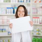 Female Pharmacist Holding Blank Paper At Pharmacy — Stock Photo