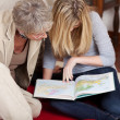 Teenage girl with her grandmother reading maps — Photo