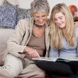 Grandmother and granddaughter reading a book — Stock Photo