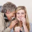 Stock Photo: Grandmother and granddaughter giggling together